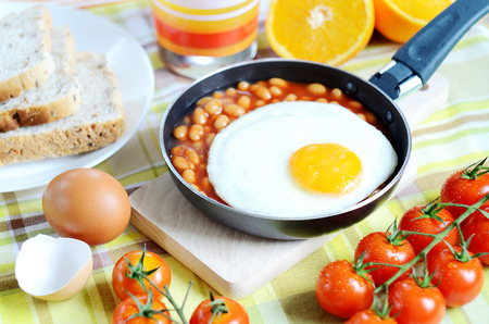 breadboard: Breakfast, fried egg with beans in a frying pan, toast bread, fresh orange juice, tomatoes and a wooden breadboard on a green tablecloth