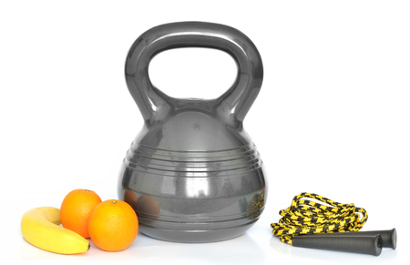 calisthenics: Isolated modern design kettlebell - 10kg, fresh fruit (banan, oranges) and yellow jumping rope on white background