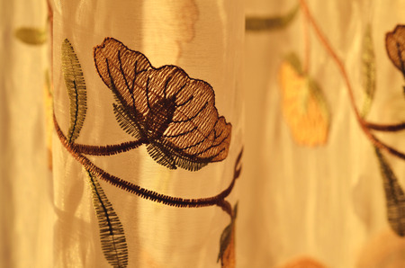 draped cloth: Close-up detail of luxury draped golden decorative curtain with flowers ornamental indoors at sunset