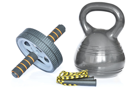 calisthenics: Isolated modern design kettlebell - 10kg, ab wheel and yellow jumping rope on white background