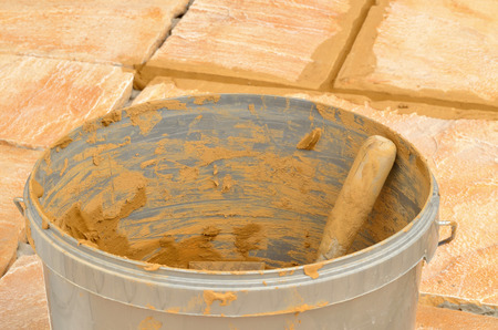 grout: Bucket with grout on concrete outdoor tiles, sandstone colored paving on the terrace with brown not dry joints