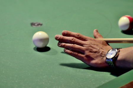 billiards rooms: Close-up of pool player hits the cue ball