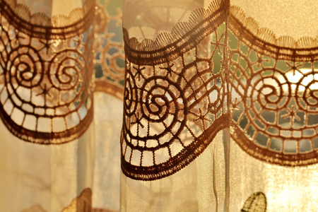 draped: Close-up detail of luxury draped golden decorative curtain with flowers ornamental indoors at sunset
