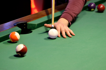 pool cue: Close-up of pool player hits the cue ball