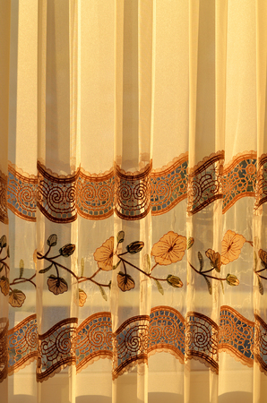 yellow tassel: Luxury draped golden decorative curtain with flowers ornamental indoors at sunset