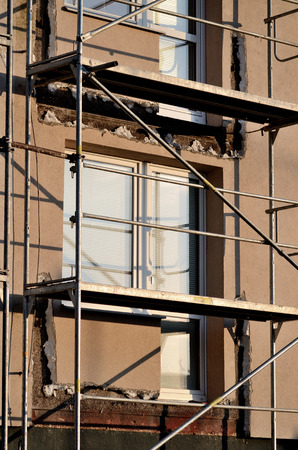 thermo: Scaffolding in building external thermo insulation protection - construction Stock Photo