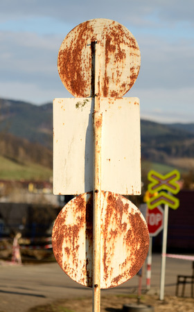 Back side of old rusty traffic sign at sunset light