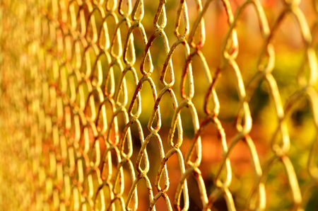 Old rusty chain-link fence at orange sunset Stock Photo