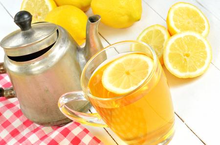 Chá preto com fatia de limão na caneca de vidro, bule de chá velho, toalha de xadrez vermelha e limões em primeiro plano Foto de archivo - 74339322