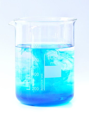 Dissolution process blue chemicals in water in glass chemical beaker