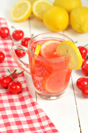 close up food: Fruit cherry tea with slice of lemon in glass mug, red checkered tablecloth, teaspoon sugar, fresh cherries and lemons in foreground