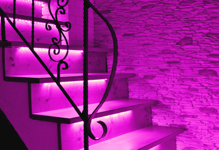 Violet, purple LED lighting wooden stairs with antique railing Stock Photo
