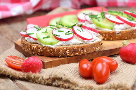 Wholemeal grain bread with curd cheese, fresh radish, cucumber and tomatoes on a wooden cutting board - concept of healthy fitness breakfast or snack 免版税图像 - 103290315