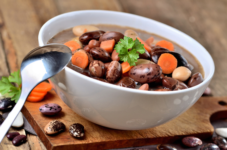 Close-up of bowl of bean soup with large beans , spoon, carrots, parsley and marjoram