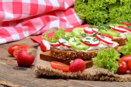 Wholemeal grain bread with curd cheese, fresh radish, cucumber and tomatoes on a wooden cutting board - concept of healthy fitness breakfast or snack, fresh salad in the background 免版税图像 - 105523923