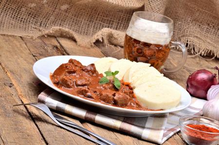 Carne di gulasch di maiale con gnocchi sul piatto bianco, posate, birra fredda, aglio, cipolla, pepe, tovaglia in background - tipica cucina ceca