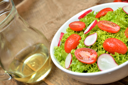 Close-up of green salad Lollo Biondo with tomatoes and radishes in a white bowl on wooden table and pitcher of oil