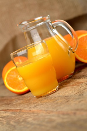 Glass full of orange juice, carafe with fresh juice and fresh oranges in the background on wooden table - vertical photo