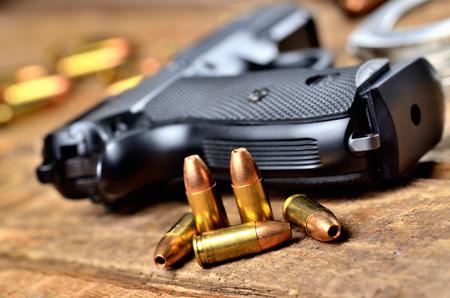 Close-up of 9mm handgun, bullets and handcuffs