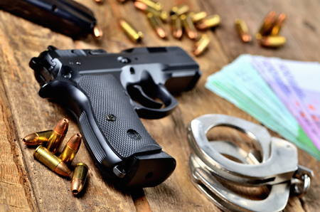 9mm pistol, bullets, magazine and euro banknotes on old wooden table