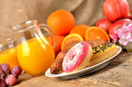 Sweet breakfast, donuts, oranges and orange juice and spring flowers on wooden table
