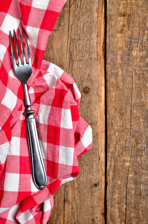 Fork on red checkered tablecloth right frame on vintage wooden table background - view from above - vertical photo