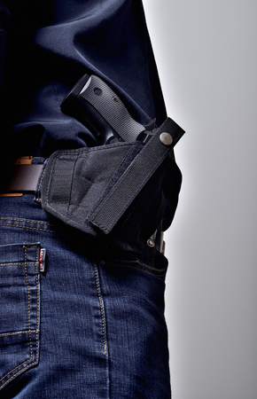 Textile holster with a pistol gun on the belt, blue jeans, a black shirt Standard-Bild