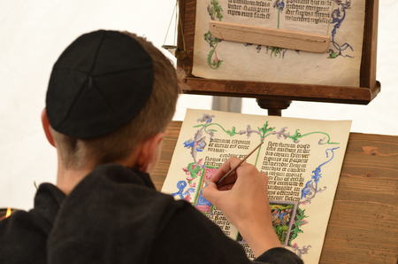 Young male medieval scribe make manuscript - calligraphy 스톡 콘텐츠