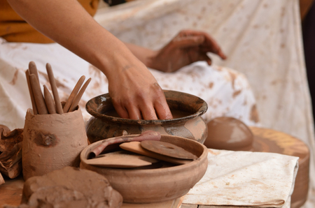 Close-up of female hand of medieval craftsman potter preparing clay - moistens and kneads the clay before work