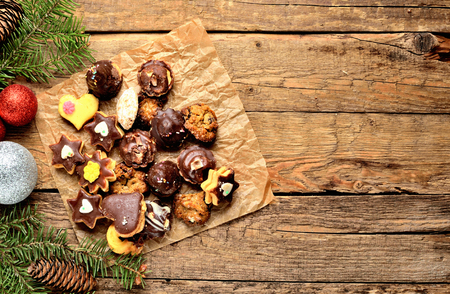 Top view of christmas sweets with different types of candy on baking paper and Christmas decorations in background Imagens
