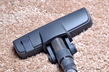 Head of vacuum cleaner on shaggy carpet - close-up of noozle