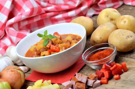 Potato and sausage goulash, pepper, onion and garlic on wooden table Imagens