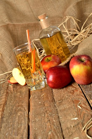 Homemade apple juice with ice, red apples, straw, still life on a wooden table vertical photo Imagens