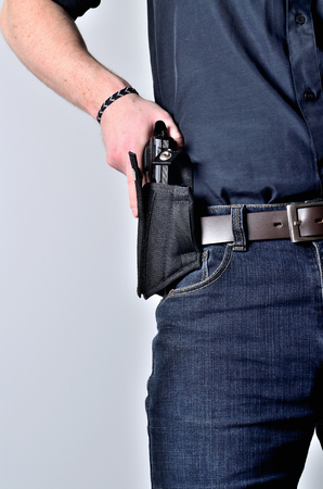 Man pulling out a pistol gun from the holster on belt, blue jeans, black shirt Imagens