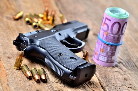9mm handgun, bullets and roll of euro banknotes Imagens