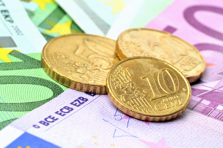 Ten, twelve and thirty euro cents coins on euro banknotes Imagens