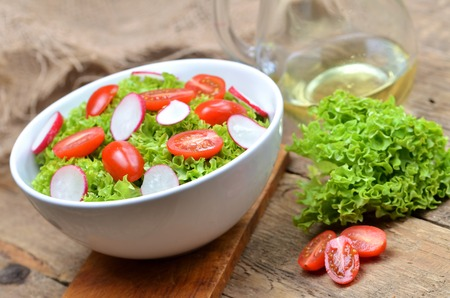Green salad Lollo Biondo with tomatoes and radishes in a white bowl on wooden table, a pitcher of oil in the background