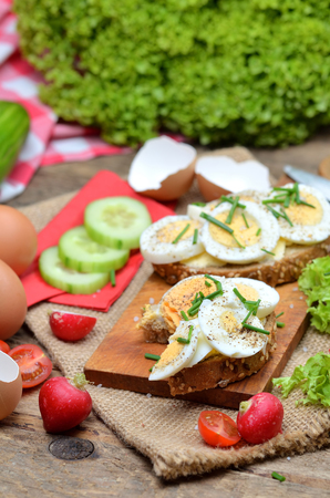 Wholegrain bread with butter, hard-boiled eggs, fresh radishes, tomatoes, salad and cucumbers in background, vertical photo Imagens