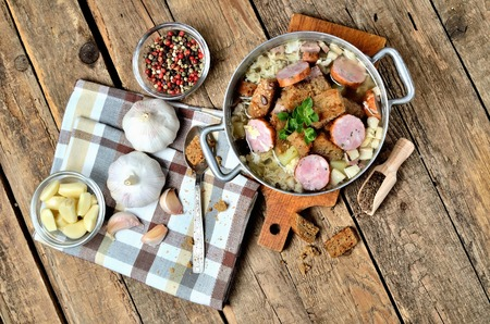Top view of garlic soup in an old saucepan, sausage, fresh garlic bulbs, cloves, colored pepper, wooden spoon, croutons and a towel on a rustic wooden table