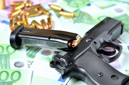 Close-up of pistol gun, loaded magazine and bullets on euro banknotes background Imagens