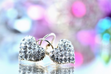 Pair of heart shaped earring decorated with diamonds on glass and elegant reflection - colored background blue and purple