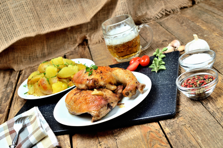 Golden grilled chicken legs on a plate, roasted potatoes and cold beer, rosemary, tomatoes, oregano, salt, pepper and garlic on a wooden table