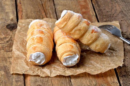 Custard tube of pastry filled with cream - dessert cake - traditional czech sweet on baking paper on wooden table