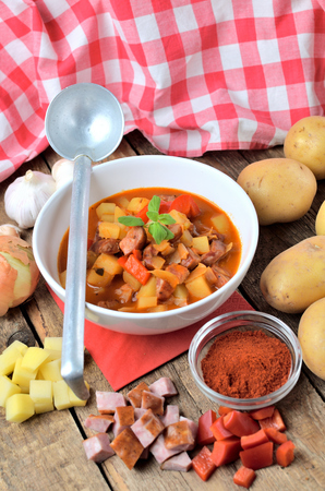 Potato and sausage goulash in dish, pepper, garlic, onion and ladle on wooden table vertical photo