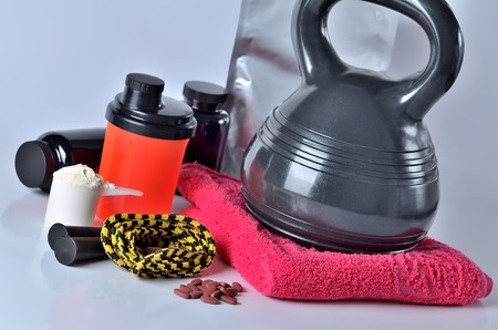 Protein powder, vitamines, shaker protein pack, jump rope, towel and kettlebell - fitness concept, isolated Imagens