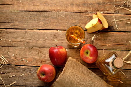 View from above of homemade apple juice with ice, red apples, straw, still life on a wooden table