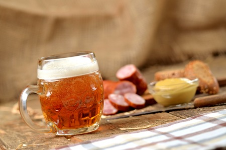 Glass of beer, sausage, mustard and bread in the background