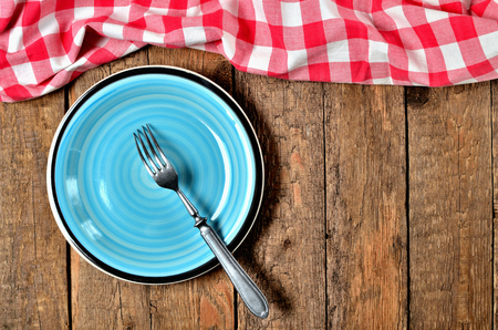 Fork in blue ceramic plate and red checkered tablecloth top frame on old vintage wooden table background - view from above