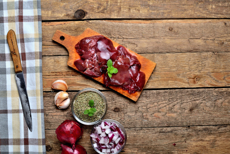 View from above of raw chicken liver on a wooden cutting board, fresh garlic, dried marjoram, oregano, onion, knife and brown checkered tablecloth left frame