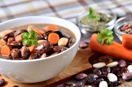 Bowl of bean soup with large beans on cutting board, carrots, parsley, marjoram, spoon and ladle, towel in background